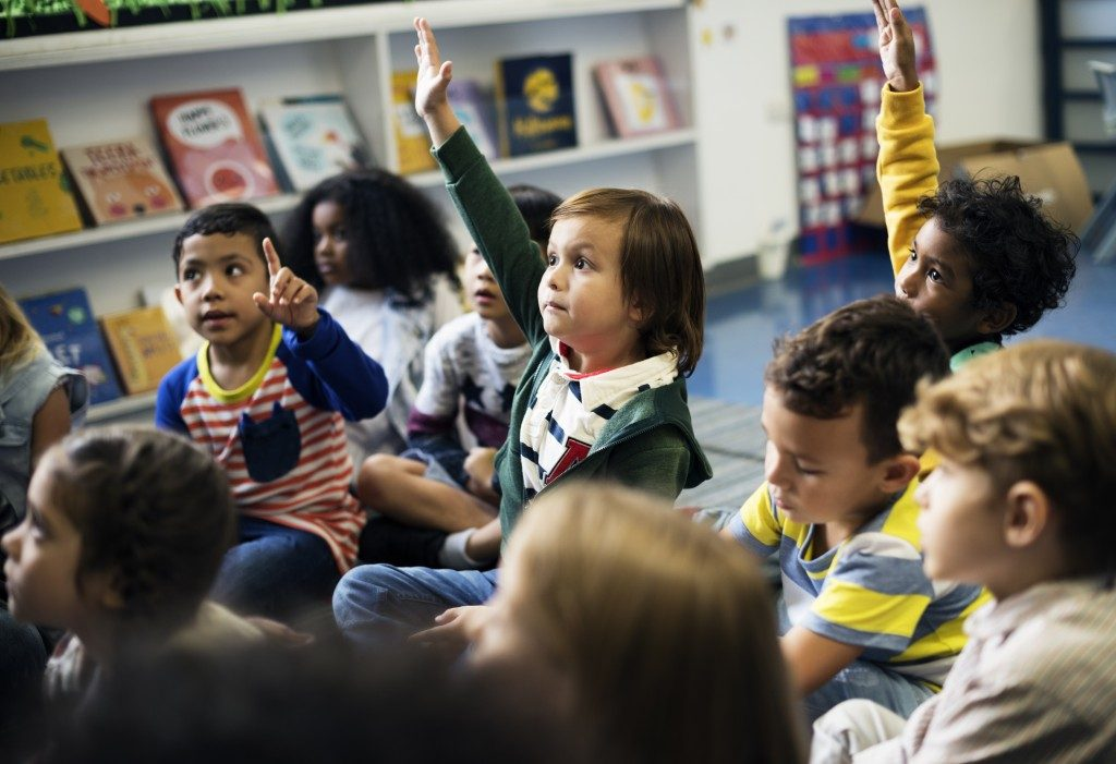 children raising their hands in their class