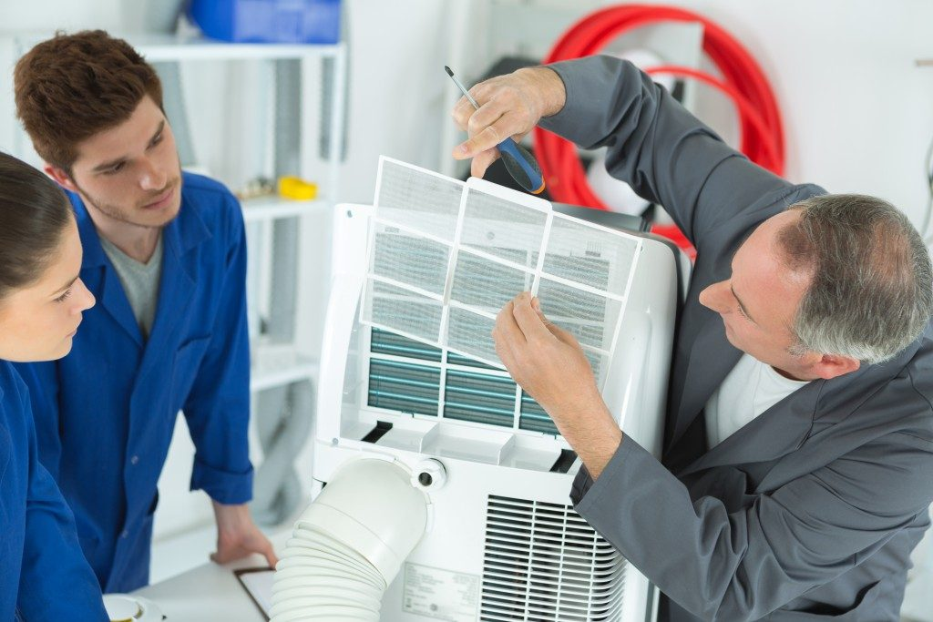 Technicians checking on the air conditioning unit