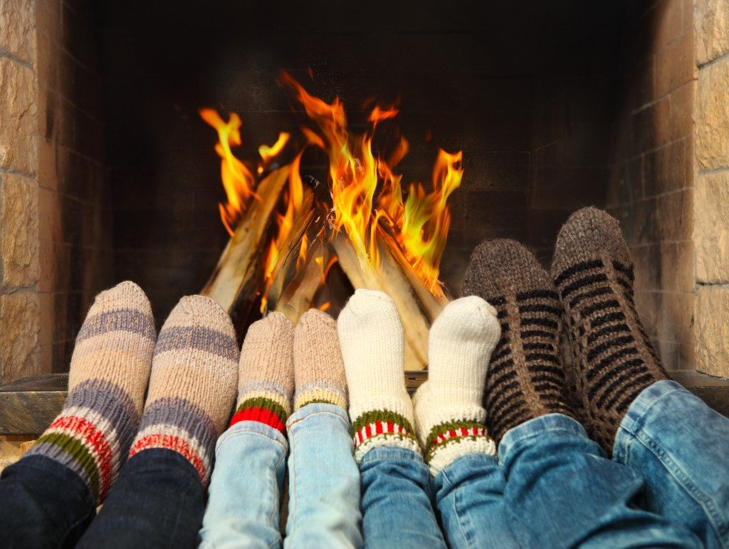 people wearing socks by the fireplace