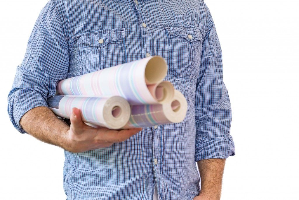 a man holding some wallpaper