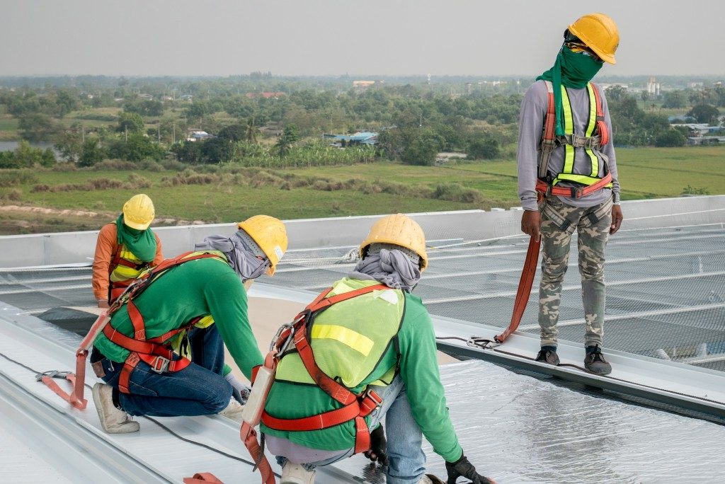 men at work laying down foil sheets on the roof