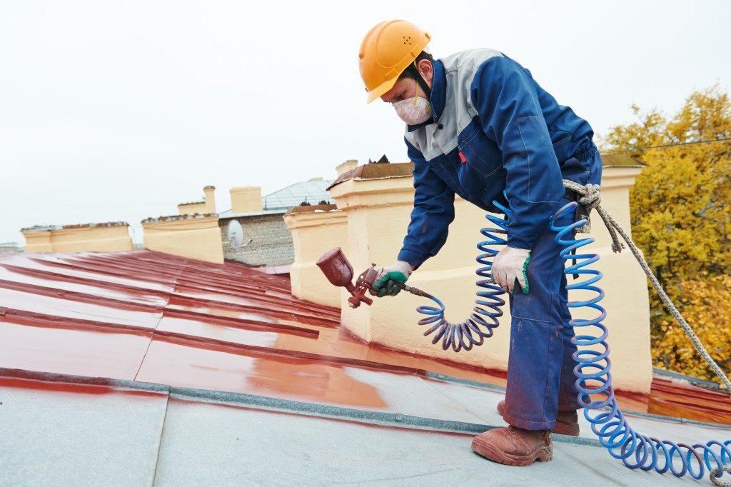 man spray painting metal sheet roofing