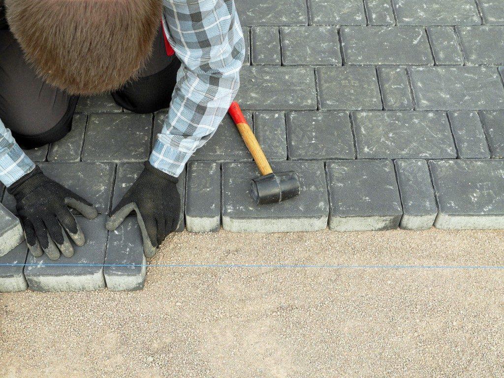 man installing concrete blocks
