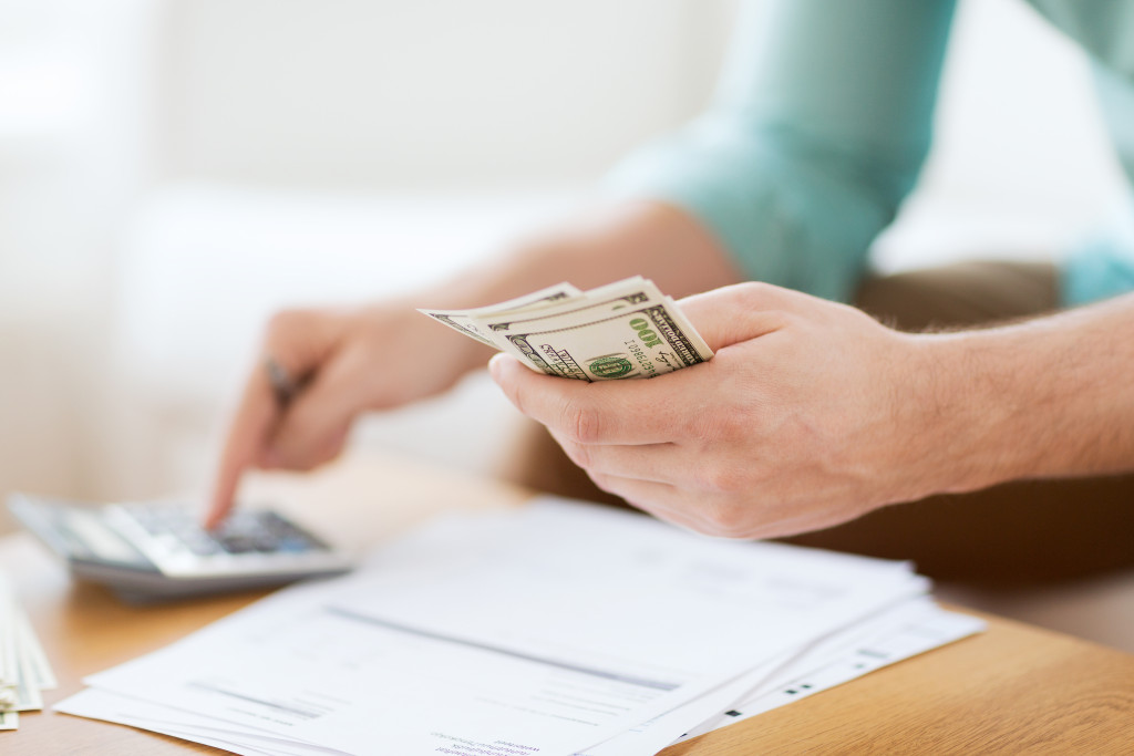 man holding cash computing costs