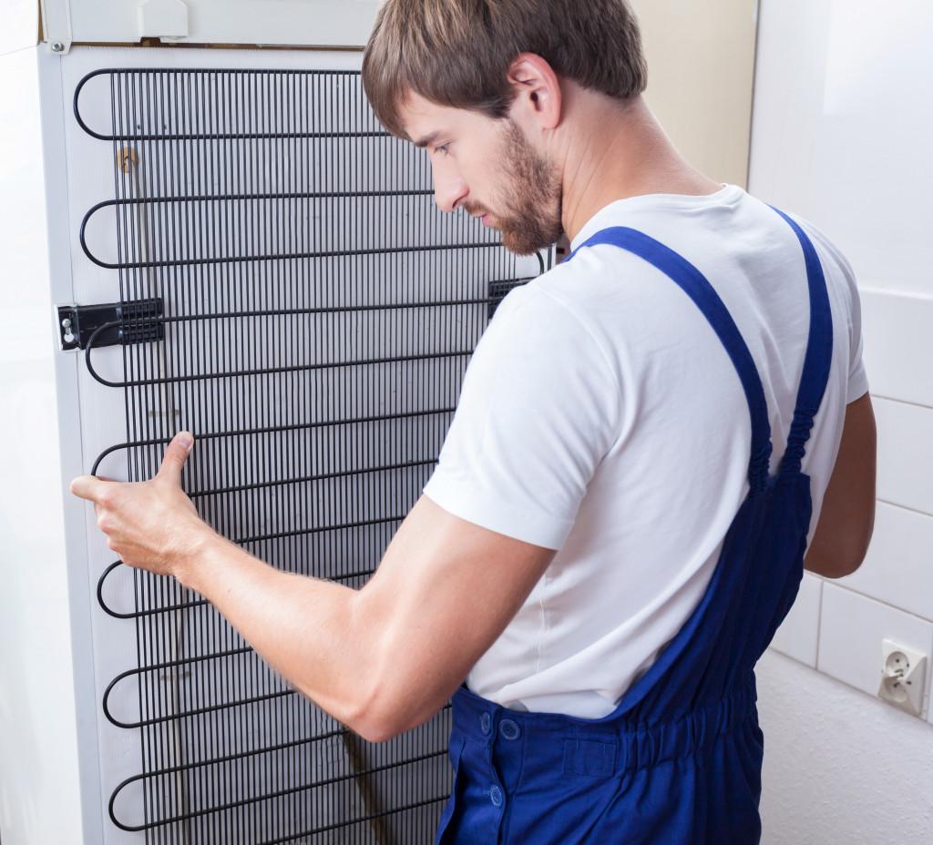 man fixing a fridge
