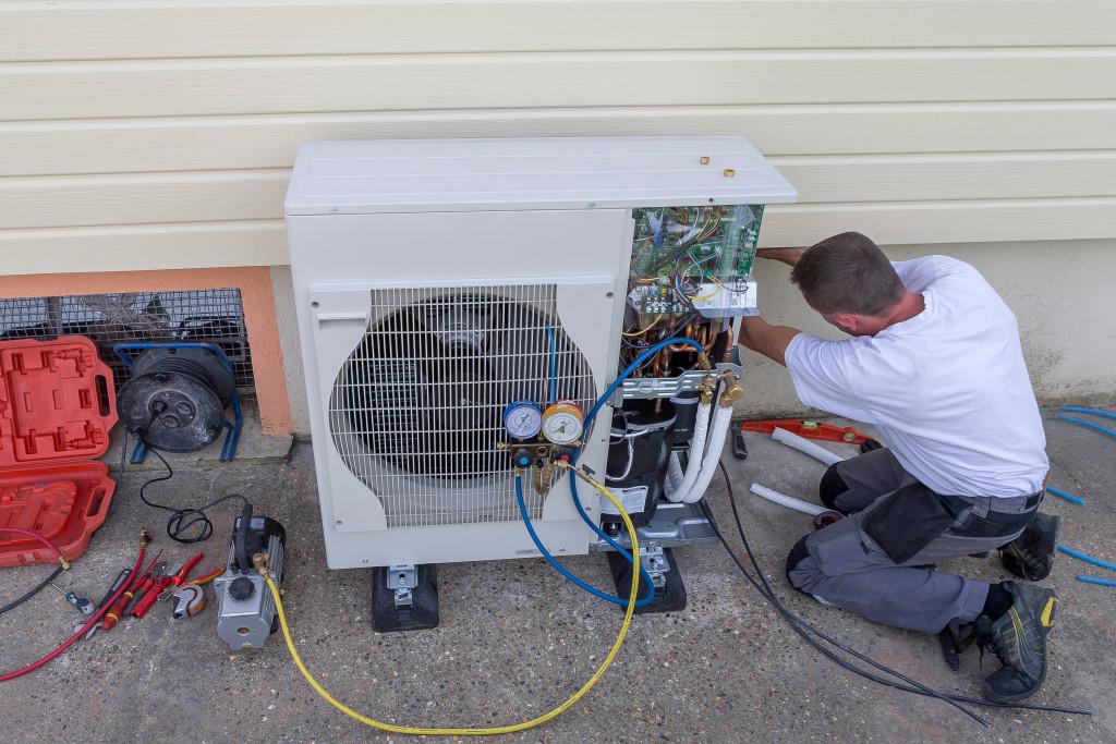 man fixing an HVAC unit